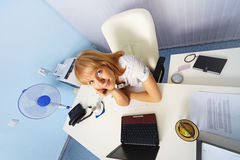Funny young woman sitting in an office Royalty Free Stock Image
