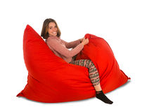 Funny young woman sitting on red beanbag sofa chair isolated on Royalty Free Stock Images