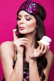 Funny young woman in sleeping mask and pajamas, sweets on pink background. beauty face. Royalty Free Stock Images