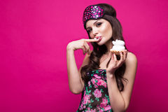 Funny young woman in sleeping mask and pajamas, sweets on pink background. beauty face. Royalty Free Stock Photography