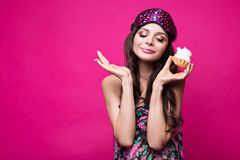 Funny young woman in sleeping mask and pajamas, sweets on pink background. beauty face. Royalty Free Stock Photos
