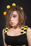Funny young woman in studio with yellow balls. On black background stock photography