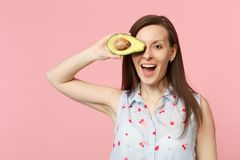 Funny young woman in summer clothes covering eye with half of fresh ripe avocado fruit isolated on pink pastel. Background in studio. People vivid lifestyle royalty free stock photos