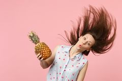 Funny young woman in summer clothes with flowing hair holding fresh ripe pineapple fruit isolated on pink pastel wall. Background. People vivid lifestyle, relax stock images