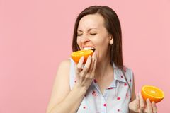 Funny young woman in summer clothes keeping eyes closed biting half of fresh ripe orange fruit isolated on pink pastel. Background. People vivid lifestyle relax stock image