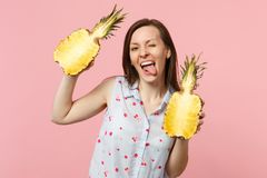 Funny young woman in summer clothes showing tongue holding halfs of fresh ripe pineapple fruit isolated on pink pastel. Background. People vivid lifestyle royalty free stock photography