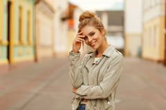 Funny young woman with a sweet smile in a fashionable jacket. Walks in the city royalty free stock photos
