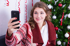 Funny young woman taking selfie photo with mobile phone near chr Stock Images