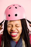 Funny woman wearing Cycling Helmet portrait pink background real Stock Photo