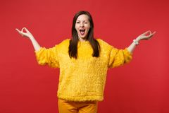 Funny young woman in yellow fur sweater blinking hold hands in yoga gesture keeping mouth wide open isolated on red royalty free stock image