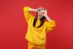 Funny young woman in yellow fur sweater holding hands near eyes, imitating glasses or binoculars isolated on bright red. Wall background. People sincere royalty free stock photo