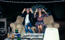 Funny young women holding smartphones showing male Royalty Free Stock Images