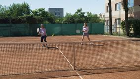 Young women playing doubles at a tennis court. Funny young women playing doubles at a tennis court stock video