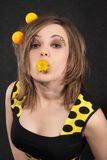 Funny young women with yellow balls in hair. Studio portrait of funny young women with yellow balls in hair on black background royalty free stock photo