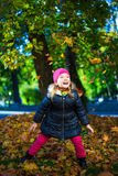 Funnyl little girl playing with maple leaves in park Stock Images