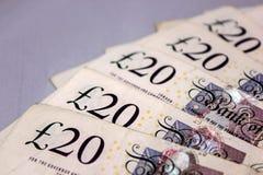 20 funtów gotówki dla podróży lub oszczędzanie na stole Zdjęcia Stock