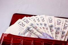 20 funtów gotówki dla podróży lub oszczędzanie w czerwonej kiesie Obrazy Royalty Free