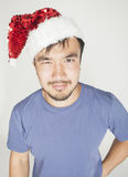 Funy exotical asian Santa claus in new years red hat smiling Royalty Free Stock Image