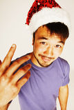 Funy exotical asian Santa claus in new years red hat smiling Stock Photo