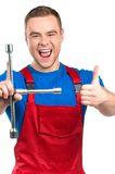Funy mechanic standing and holding wrench. Stock Photos