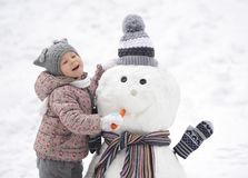 Funy street portrait of a girl feeding the snowman with a carrot Royalty Free Stock Photo