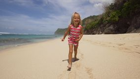 Funzionamenti del bambino lungo la spiaggia Immagine Stock
