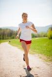 Funzionamenti del corridore della donna - allenamento in primavera Immagini Stock