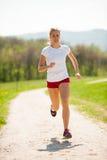 Funzionamenti del corridore della donna - allenamento in primavera Fotografia Stock