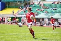 Funzionamenti del giocatore di rugby con la palla Immagini Stock Libere da Diritti