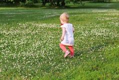 Funzionamenti della bambina attraverso un grande campo Fotografia Stock