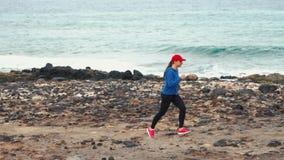 Funzionamenti della donna lungo la riva pietrosa dell'oceano Stile di vita attivo sano archivi video