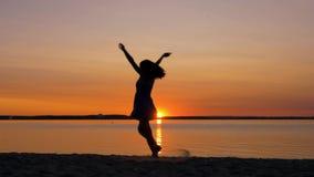 Funzionamenti della donna verso il tramonto sulla spiaggia che solleva le sue mani su e che gira intorno archivi video