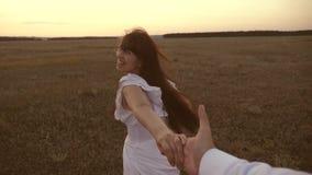Funzionamenti della ragazza attraverso il campo che tiene la mano del suoi uomo e risate cari Movimento lento felice nei funziona archivi video