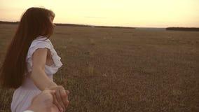 Funzionamenti della ragazza attraverso il campo che tiene la mano del suoi uomo e risate cari Movimento lento felice nei funziona video d archivio