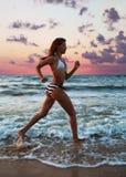 Funzionamenti della ragazza lungo la spiaggia Immagini Stock