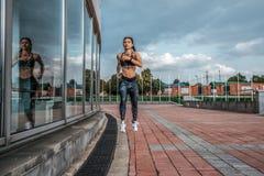 Funzionamenti muscolari della ragazza di estate in città, su un trotto di mattina, pelle abbronzata, tatuaggi Le ghette degli abi fotografia stock