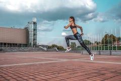 Funzionamenti muscolari della ragazza di estate in città, su un trotto di mattina, salto in alto Le ghette degli abiti sportivi c fotografie stock