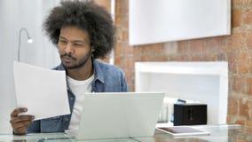 Funzionamento africano dell'uomo sui documenti nell'ufficio del sottotetto stock footage