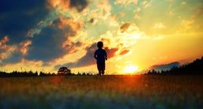 Funzionamento allegro del ragazzo verso il tramonto fotografia stock libera da diritti