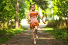 Funzionamento allegro della bambina lungo un percorso in un parco felice Fotografia Stock
