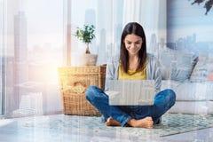 Funzionamento allegro della giovane donna mentre sedendosi a casa fotografia stock libera da diritti