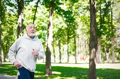 Funzionamento anziano dell'uomo nel parco verde, spazio della copia Fotografia Stock