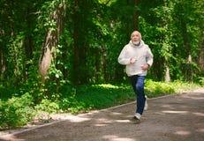 Funzionamento anziano dell'uomo nella foresta verde, spazio della copia Immagini Stock Libere da Diritti
