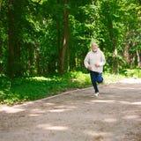 Funzionamento anziano dell'uomo nella foresta verde, spazio della copia Fotografia Stock Libera da Diritti