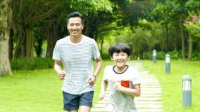 Funzionamento asiatico del padre dietro suo figlio in parco di estate al rallentatore video d archivio