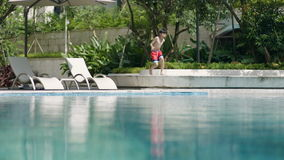 Funzionamento asiatico dell'adolescente & saltare nella piscina nel movimento lento del giardino stock footage