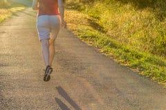 Funzionamento atletico della donna alla traccia della campagna alla luce di alba fotografia stock
