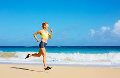 Funzionamento atletico della giovane donna sulla spiaggia Fotografia Stock