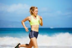 Funzionamento atletico della giovane donna sulla spiaggia Immagini Stock