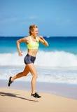 Funzionamento atletico della giovane donna sulla spiaggia Fotografie Stock Libere da Diritti